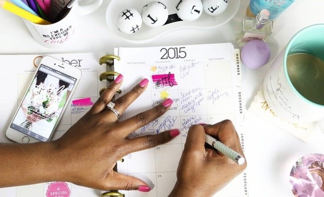 Hands writing notes in the event planner