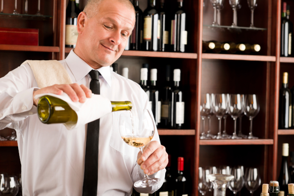 Waiter serving a wine glass